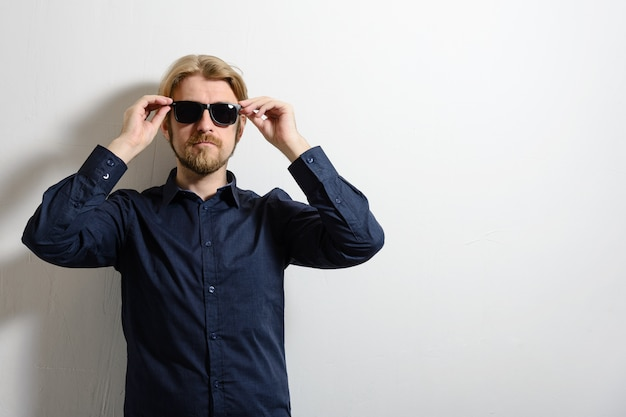 Hombre elegante con una camisa azul y gafas de sol de pie cerca de una pared blanca y una mano sosteniendo gafas