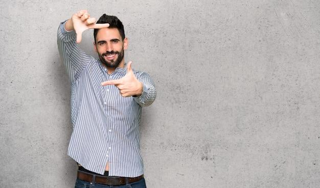 Hombre elegante con la camisa enfocando la cara. símbolo de encuadre sobre muro texturizado