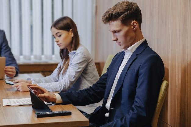 Un hombre elegante con chaqueta y camisa se sienta en el escritorio con sus colegas y trabaja con documentos en la oficina