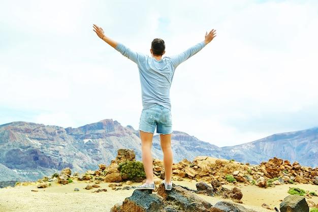 Hombre elegante feliz en ropa casual hipster de pie en el acantilado de la montaña con las manos levantadas al sol y celebrando el éxito