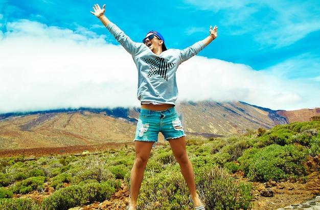 Hombre elegante feliz en ropa casual hipster saltando frente a la montaña con las manos levantadas al sol y celebrando el éxito