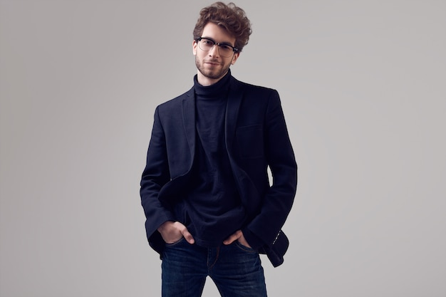 Hombre elegante guapo con el pelo rizado con traje y gafas