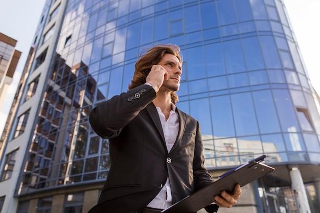 Hombre elegante hablando en el teléfono de bajo ángulo de disparo
