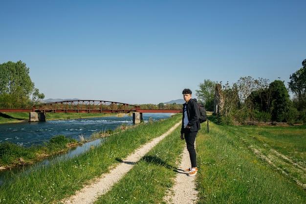 Hombre elegante joven que se coloca en camino cerca del río con la mochila que lleva
