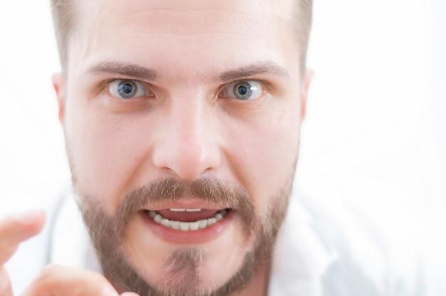Hombre elegante con una mirada loca está mirando a la cámara. el concepto de supresión, estimulación, motivación para el éxito empresarial. técnica mixta