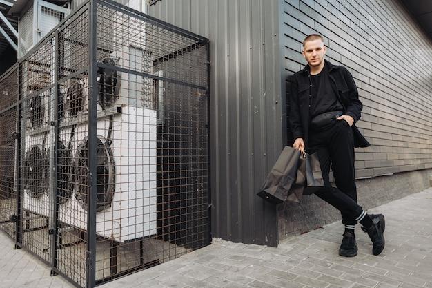 Hombre elegante en negro con bolsas de compras en black friday