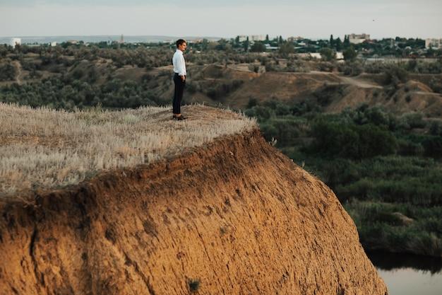 Hombre elegante de pie sobre una colina de la montaña y contemplar el paisaje con río y árboles verdes.