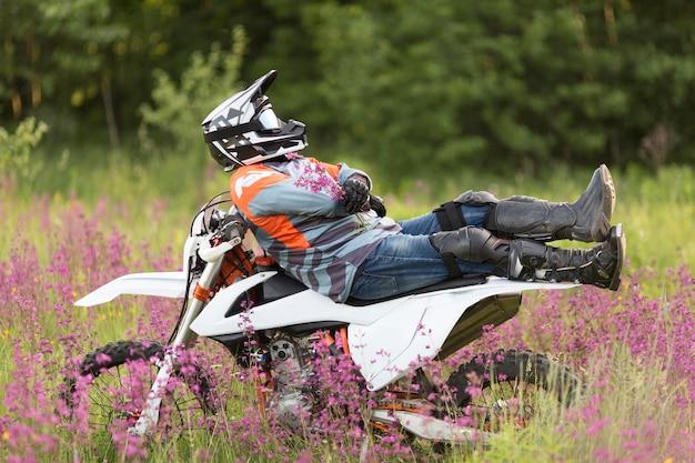 Hombre elegante que se relaja encima de la moto