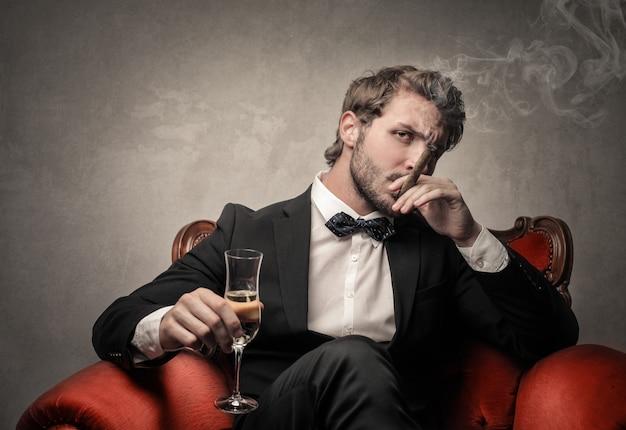 Hombre elegante rico fumando y bebiendo