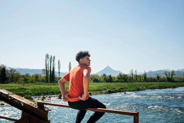 Hombre elegante sentado en la barandilla metálica del puente sobre el río