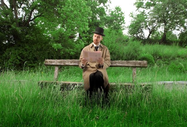 Hombre elegante en sombrero de copa que lee un periódico en un banco