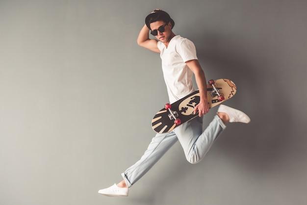 Hombre elegante está sosteniendo una patineta y mirando a cámara.