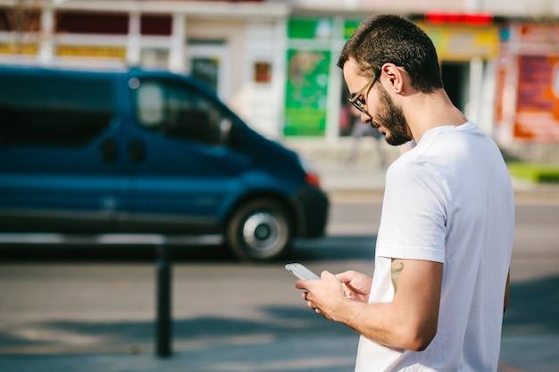 Hombre elegante con tatuaje y barba con gafas y camiseta blanca usa su teléfono inteligente