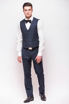 Hombre elegante en traje aislado en la pared blanca