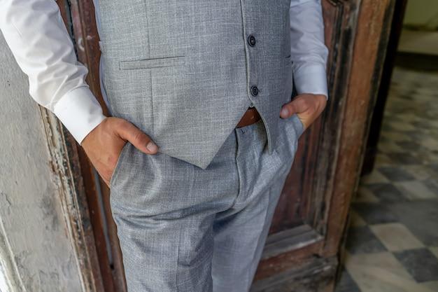 Un hombre con un elegante traje gris de cerca sin rostro.