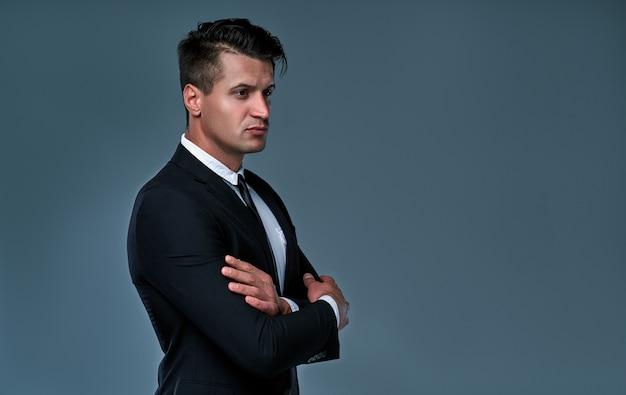 Hombre elegante vistiendo esmoquin en habitación gris