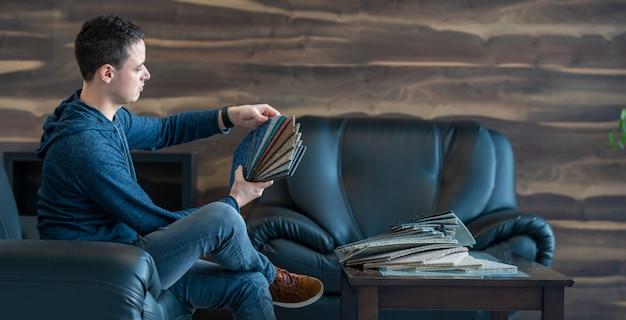 El hombre elige el color de la alfombra nueva de acuerdo con el libro de patrones en la tienda de pisos