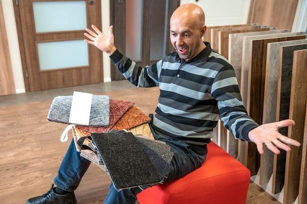 El hombre elige el color de la alfombra nueva según las muestras en la tienda de pisos