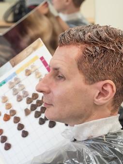 Un hombre elige pintura para teñirse el cabello. tinte de pelo.