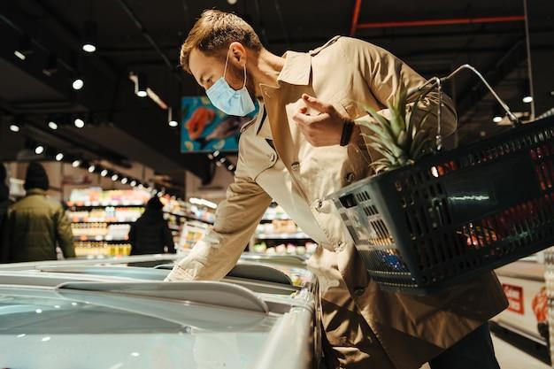 El hombre elige vino en el supermercado