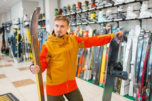 Hombre eligiendo esquí alpino y snowboard, compras