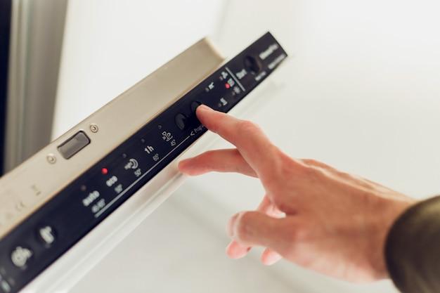 Hombre eligiendo el modo en el panel de control del lavavajillas.