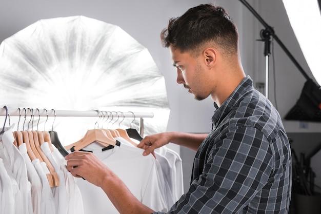 Hombre eligiendo ropa para una sesión de fotos
