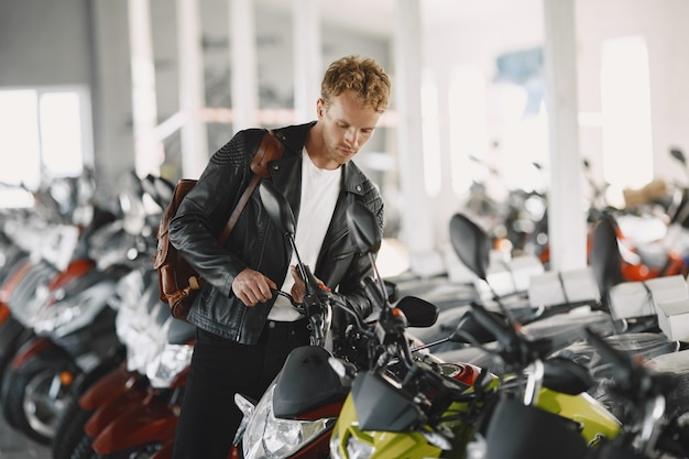 El hombre eligió motocicletas en la tienda de motos. chico con chaqueta negra.