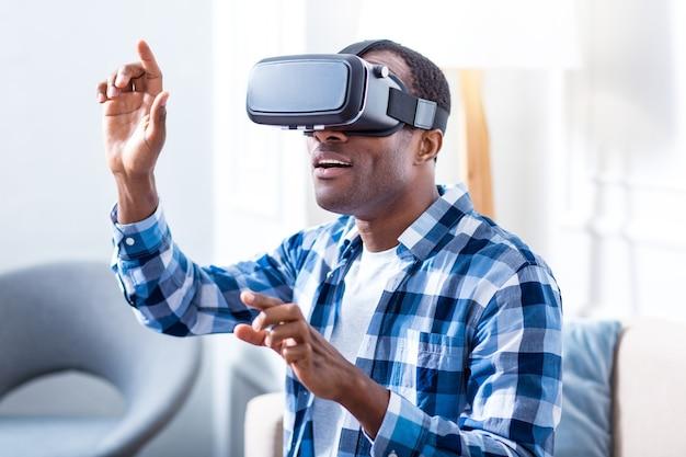 Hombre emocionado alegre positivo con gafas de realidad virtual y sonriendo mientras prueba la nueva tecnología