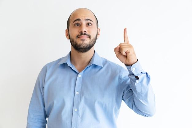 Hombre emocionado apuntando con el dedo índice hacia arriba