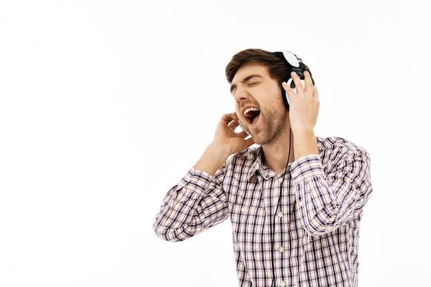 Hombre emocionado cantando en auriculares, disfruta de la música
