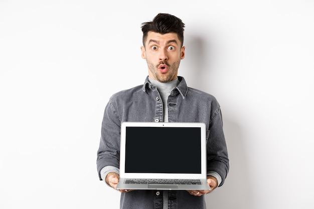 Hombre emocionado demostró la pantalla vacía de la computadora portátil, diga wow y mire a la cámara asombrado, revisando la oferta en línea, mostrando la página web, de pie sobre un fondo blanco.