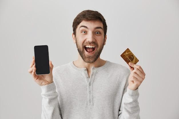 Hombre emocionado haciendo un pedido en línea, mostrando la tarjeta de crédito y la pantalla del teléfono móvil