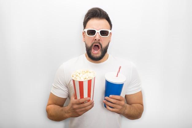 El hombre emocionado mantiene la boca abierta. él sostiene un cubo de palomitas de maíz y un vaso de cola al mismo tiempo. guy usa lentes de película.