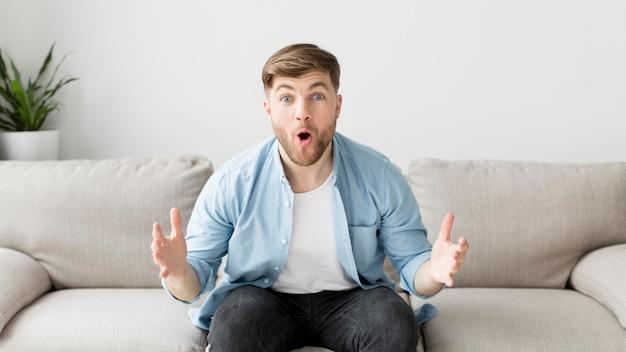 Hombre emocionado en el sofá