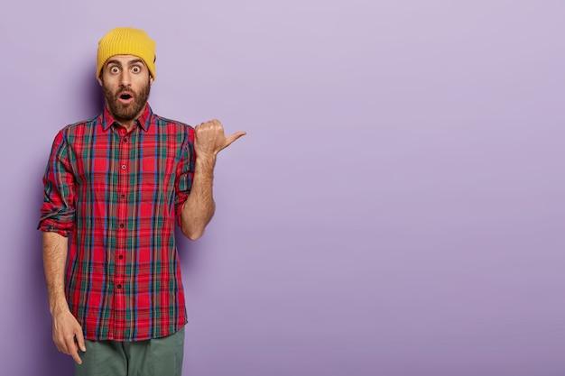 Hombre emocional asustado señala con el pulgar, viste sombrero amarillo y camisa a cuadros, anuncia algo genial
