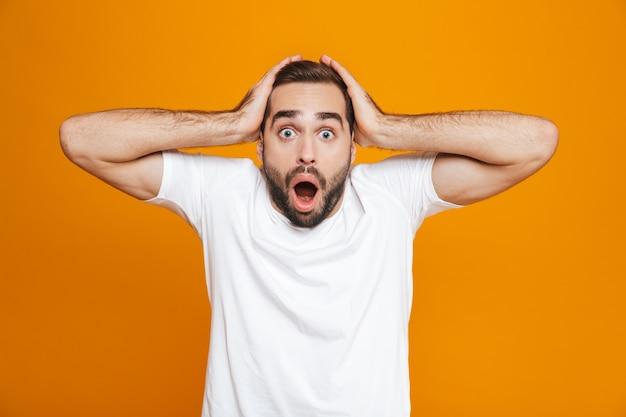 Hombre emocional con barba y bigote agarrando la cabeza mientras está de pie, aislado en amarillo