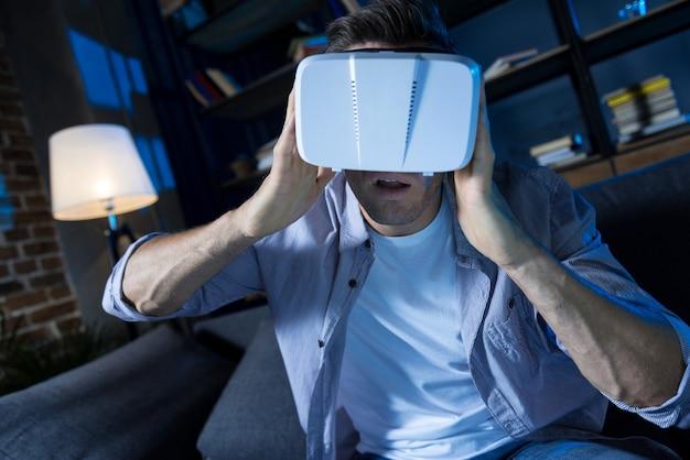 Hombre emocional inteligente joven que usa equipo especial para explorar la realidad virtual mientras está sentado en su sala de estar