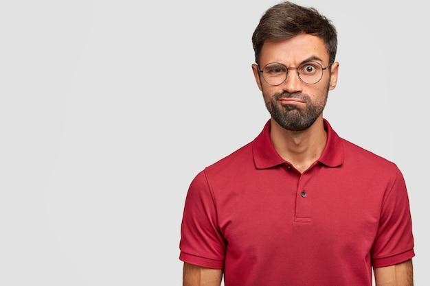 Hombre emocional joven enojado posando contra la pared blanca