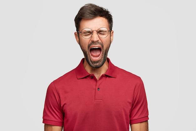 Hombre emocional joven frustrado desesperado posando contra la pared blanca