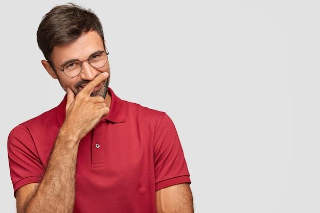 Hombre emocional joven positivo posando contra la pared blanca