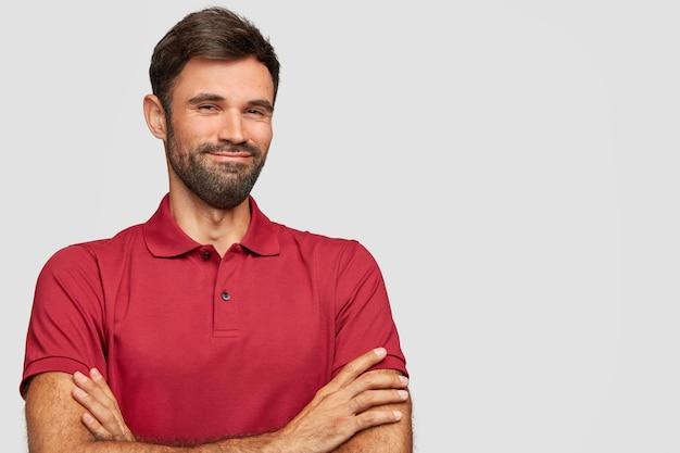 Hombre emocional joven satisfecho posando contra la pared blanca