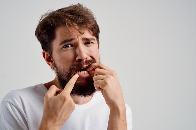Hombre emocional que se aferra a enfrentar el dolor en los dientes fondo aislado