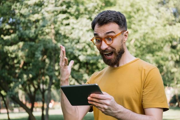 Hombre emocional con tableta digital, compras en línea, viendo películas