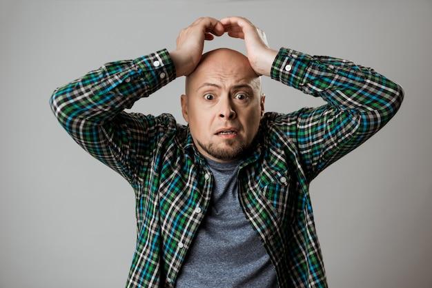 Hombre emotivo molesto agarrando su cabeza sobre la pared de color beige.