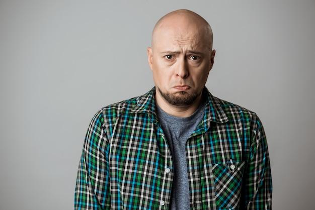 Hombre emotivo triste resentido en camisa posando sobre pared beige