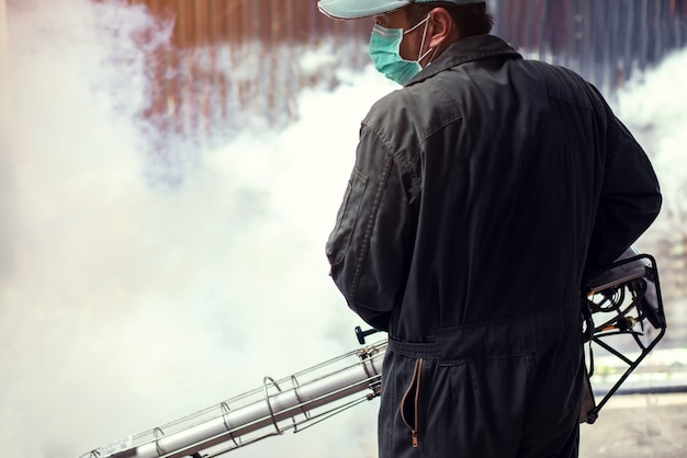 El hombre se empaña para eliminar el mosquito y prevenir la propagación del dengue y el virus del zika
