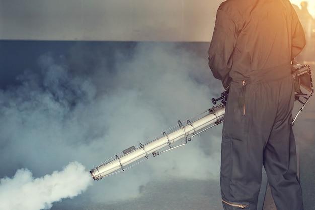 El hombre se empaña para eliminar el mosquito para prevenir la propagación de la fiebre del dengue y el virus zika