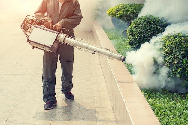 El hombre se empaña para eliminar el mosquito para prevenir la propagación de la fiebre del dengue