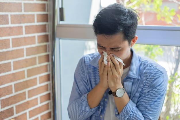 Hombre empleado frunció el ceño y estornudó mientras trabajaba en casa por coronavirus y concepto de tiempo de cuarentena
